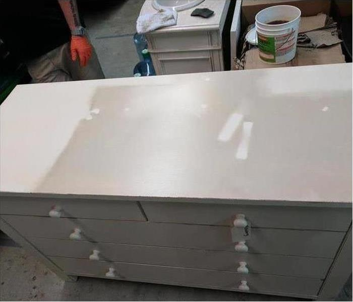 Pictured is a white bedroom dresser covered in soot that is ready for cleaning