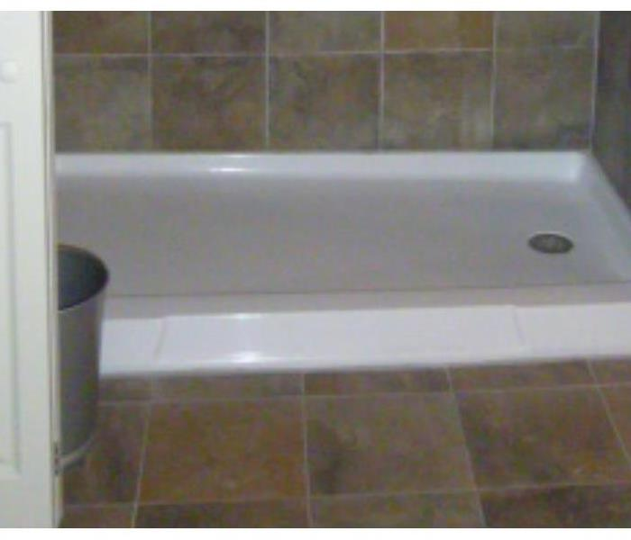 Photo taken from the same perspective after cleaning, showing a gleaming shower base and clean tile and grout