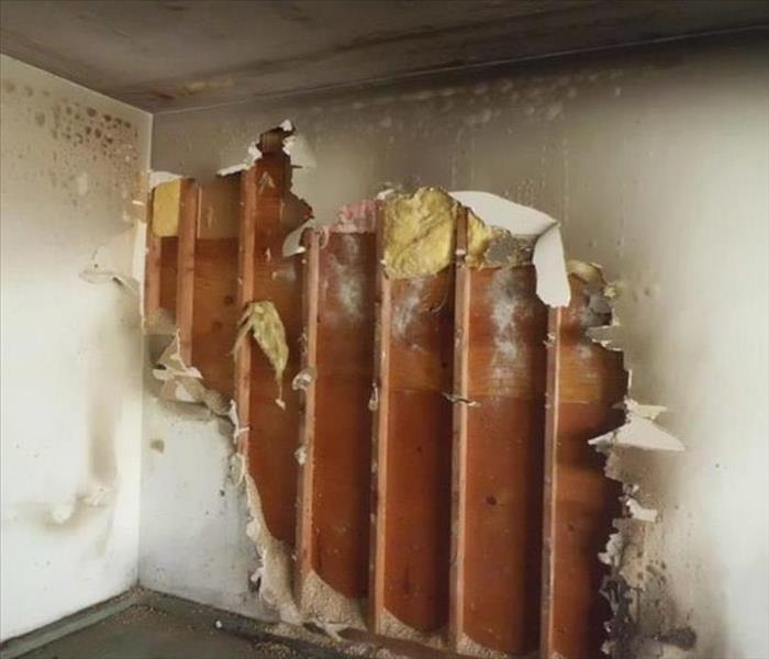 A wall in the room of a house that was damaged by a fire with drywall partially removed and some exposed insulation