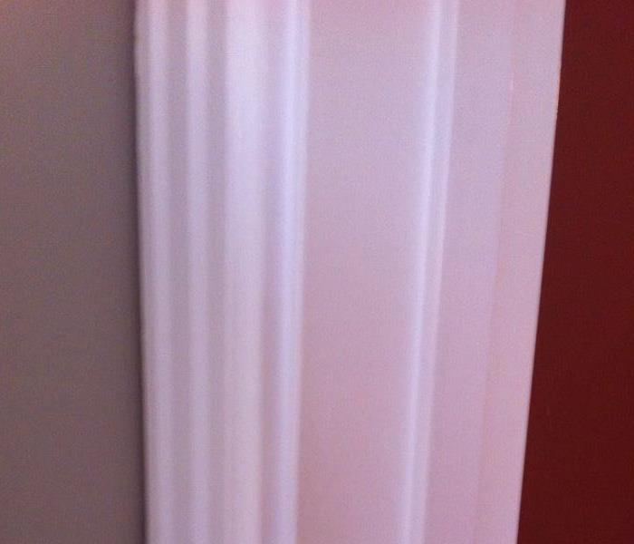 Photo of the same wall and door frame after cleaning