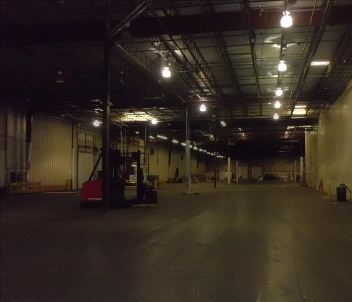empty warehouse with concrete floor and soot on walls