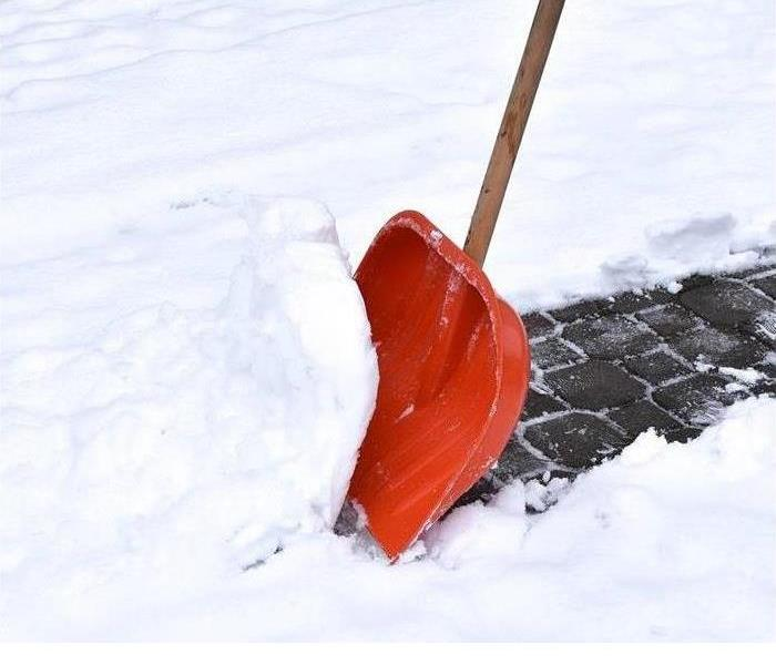 The lower part of a snow shovel moving a scoop of snow from a snow-covered sidewalk that is brick paved